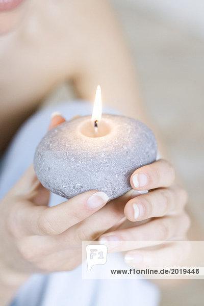 Frau mit brennender Kerze  Nahaufnahme der Hände