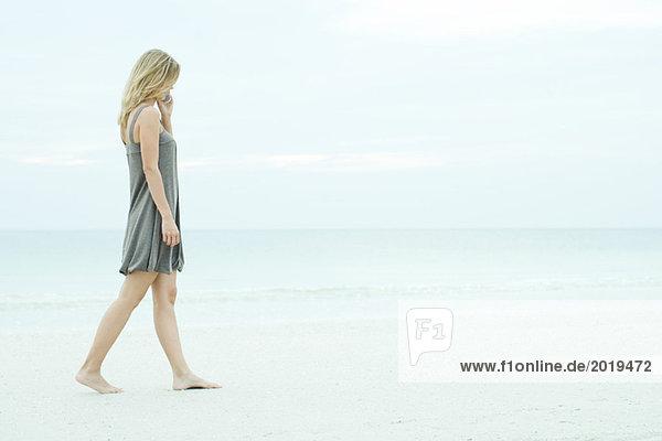 Junge Frau  die am Strand spazieren geht  mit dem Handy  volle Länge