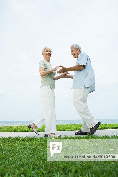 Seniorenpaar tanzt auf dem Bürgersteig mit Blick auf den Ozean  volle Länge