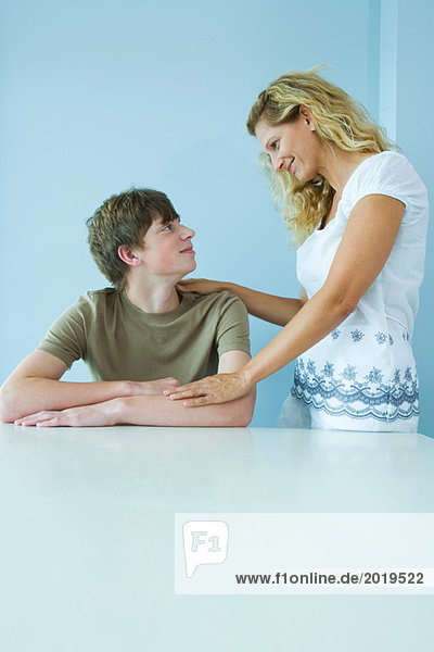 Teen boy sitting down  mother standing next to him with hand on his shoulder  smiling at each other