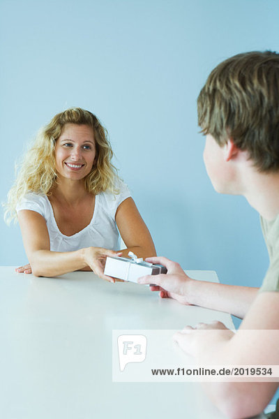 Teen boy handing mother present  both smiling at each other