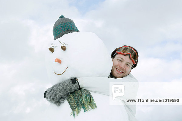 Young man hugging snowman  low angle view