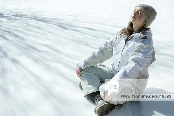 Teen girl sitting on snow  meditating