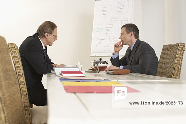 Zwei Männer sitzen am Verhandlungstisch