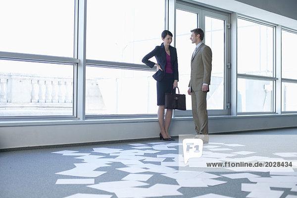 Geschäftspaar in einem leeren Büro  Seiten liegen auf dem Fußboden  fully_released