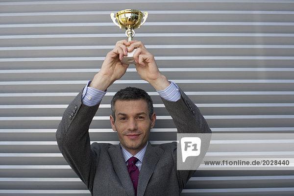 Geschäftsmann hält einen Pokal nach oben  fully_released