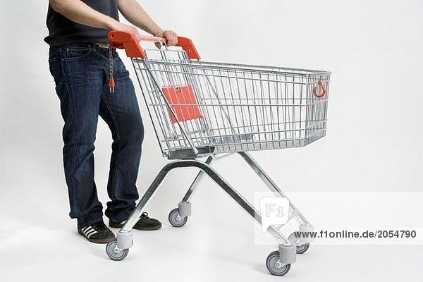 Ein Mann  der einen Einkaufswagen schiebt.