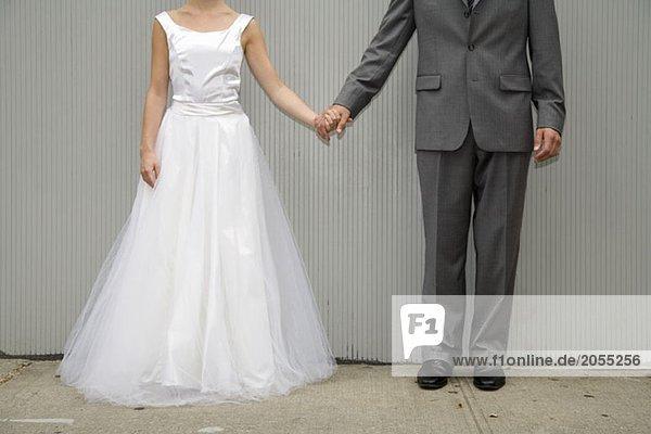 Eine Braut und ein Bräutigam  die Händchen halten.