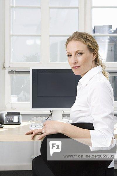 Eine Geschäftsfrau sitzt am Schreibtisch.