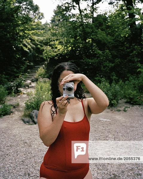 Eine Frau beim Fotografieren im Garten