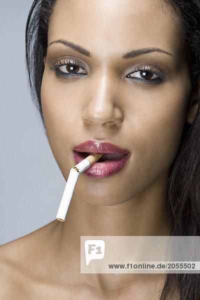 Eine Frau mit einer kaputten Zigarette im Mund.