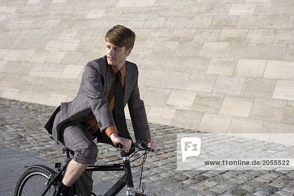 Ein Geschäftsmann  der Fahrrad fährt.