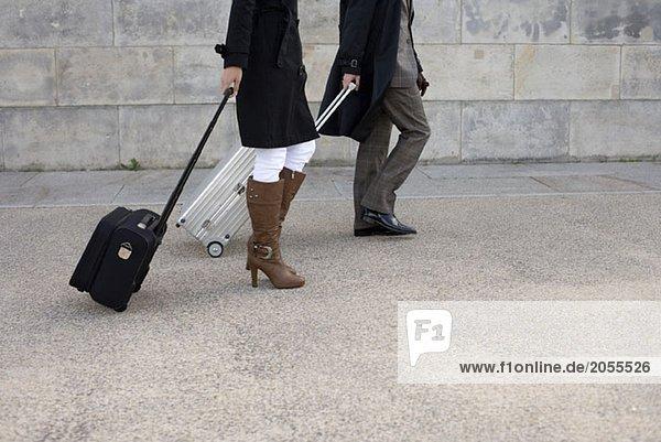 Zwei Personen  die mit Gepäck gehen