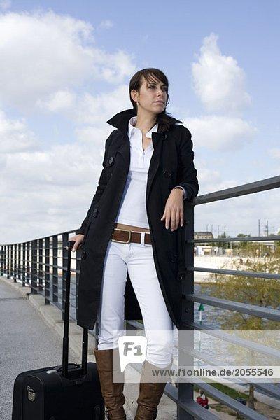 Eine Frau steht auf einer Brücke über einen Fluss mit Gepäck.