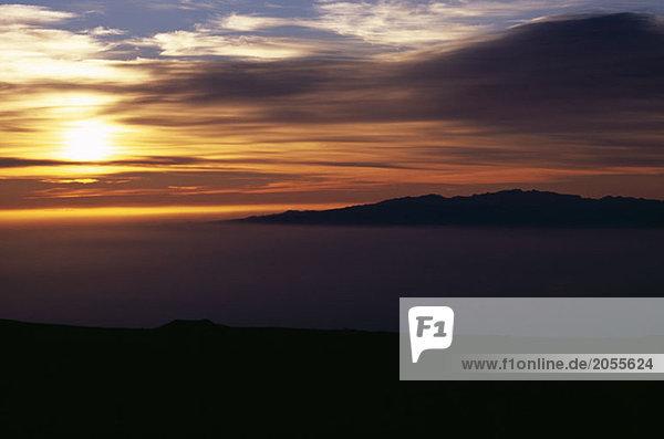 Niedrige Wolken über Hügeln bei Sonnenuntergang
