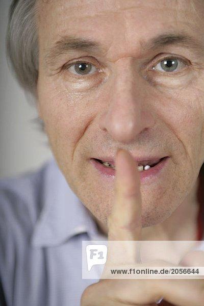 Älterer Mann mit dem Zeigefinger an den Lippen