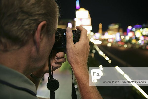 Ein älterer Mann macht ein Foto von den Straßen Las Vegas  nachts