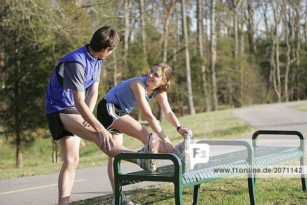 Ein Mann und eine Frau machen Stretchingübungen an einer Parkbank