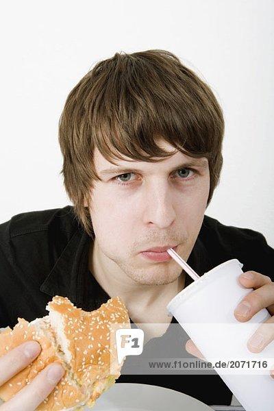 Ein junger Mann isst einen Hamburger und trinkt ein Softgetränk