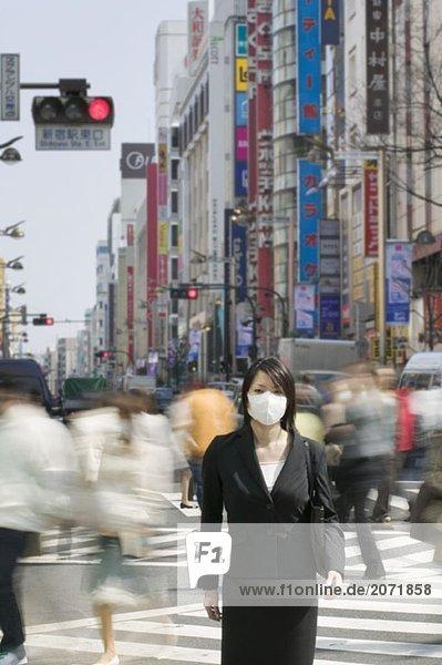 Eine Geschäftsfrau mit Mundschutz steht auf einem Zebrastreifen in der belebten Innenstadt  Tokio  Japan
