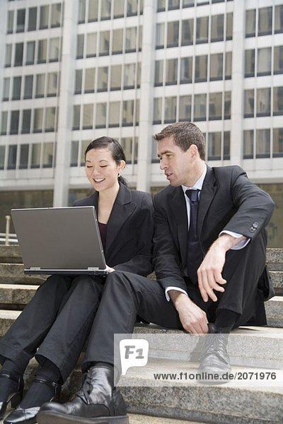 Ein Geschäftsmann und eine Geschäftsfrau mit Laptop auf den Treppen vor einem Bürohaus