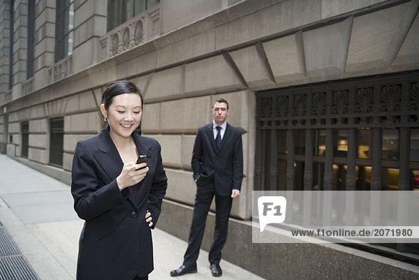 Eine Geschäftsfrau telefoniert mit einem Mobiltelefon während im Hintergrund ein Geschäftsmann wartet