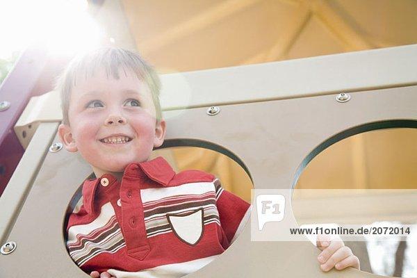 Ein kleiner Junge schaut durch ein Guckloch auf einem Spielplatz Ein kleiner Junge schaut durch ein Guckloch auf einem Spielplatz