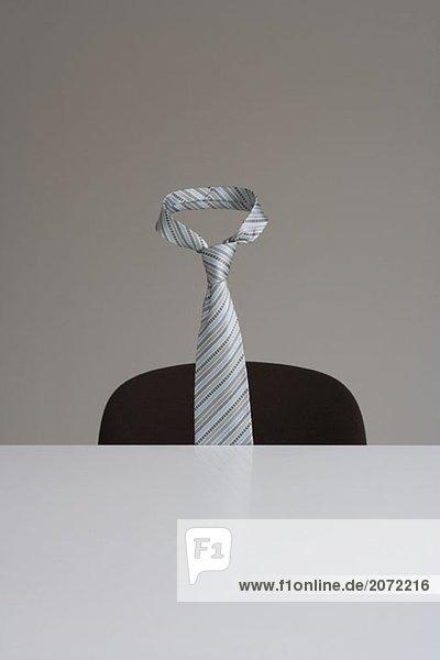 Eine Krawatte in der Luft schwebend hinter einem Schreibtisch