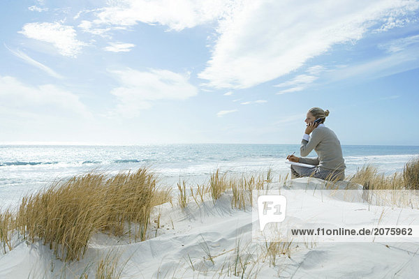 Woman sitting on dunes at beach  using cell phone