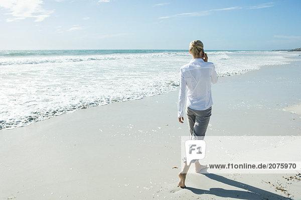 Frau barfuss laufen auf Strand  mit Handy  Rückansicht