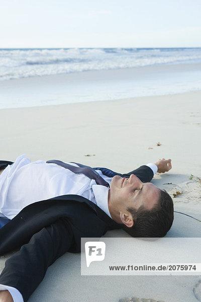 Kaufmann liegend auf Sand am Strand