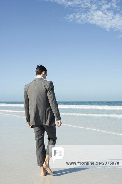 Kaufmann barfuss laufen auf Strand  Rückansicht