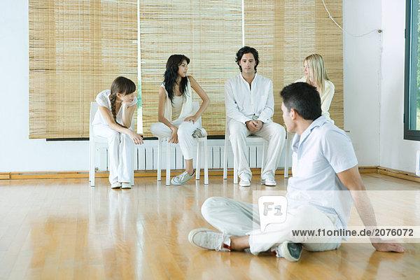 Mann sitzen auf Boden  übermäßigschulter sitzen auf Stühlen-Gruppe