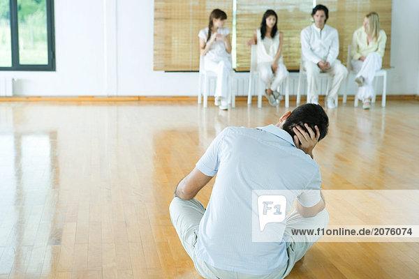 Mann sitzen auf Boden  facing Gruppe sitzen auf Stühlen