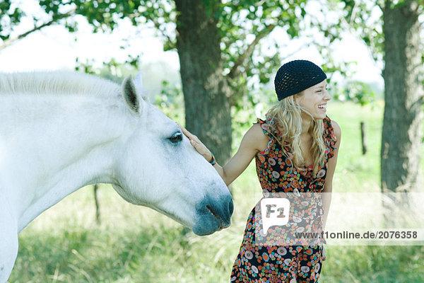 Junge Frau berühren Pferd und lachen