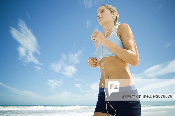 Junge Frau joggen am Strand  MP3-Player  Flachwinkelansicht anhören