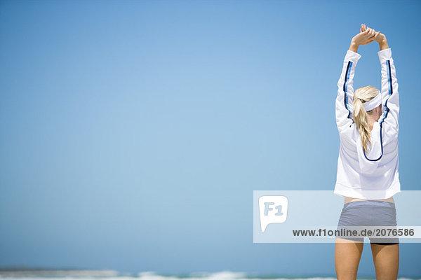 Junge Frau im active Wear auf Strand  Rückansicht