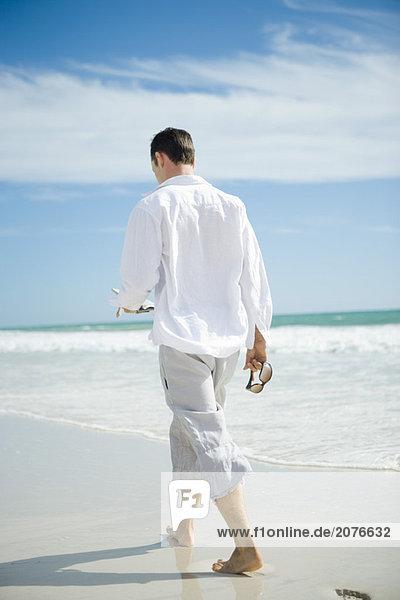 Junge Mann zu Fuß am Strand  Rückansicht