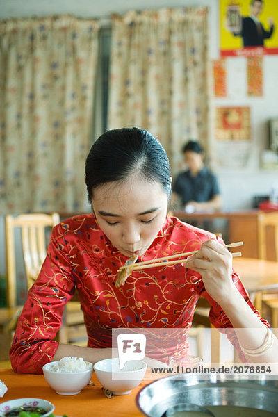 Junge Frau tragen traditionellen chinesischen Kleidung  Essen mit Stäbchen