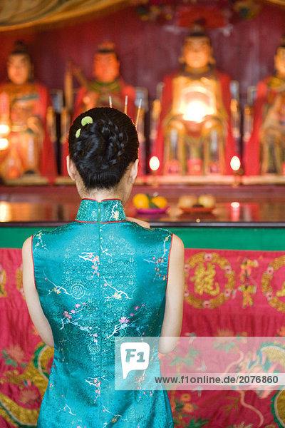 Junge Frau tragen traditionellen chinesischen Kleidung  vor der Schrein  Rückansicht