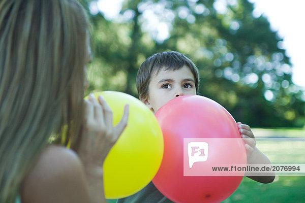 Junge und Mutter Sprengung Ballons
