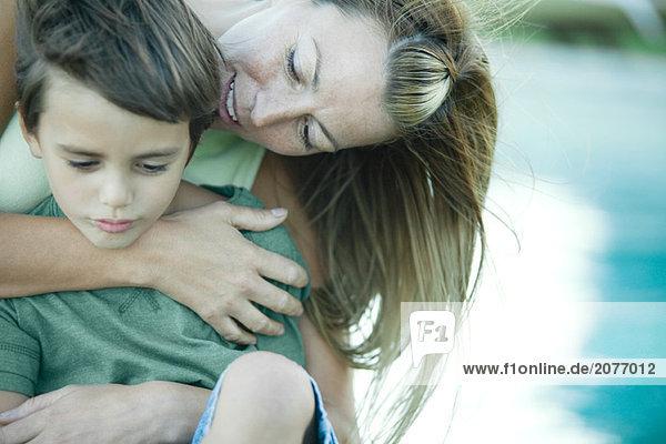 Junge und Mutter  Frau umarmt  Sohn von hinten