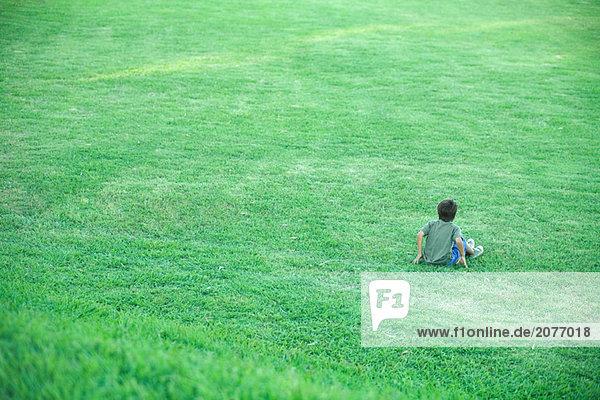 Junge sitzt im Gras  erhöhte Ansicht  voller Länge