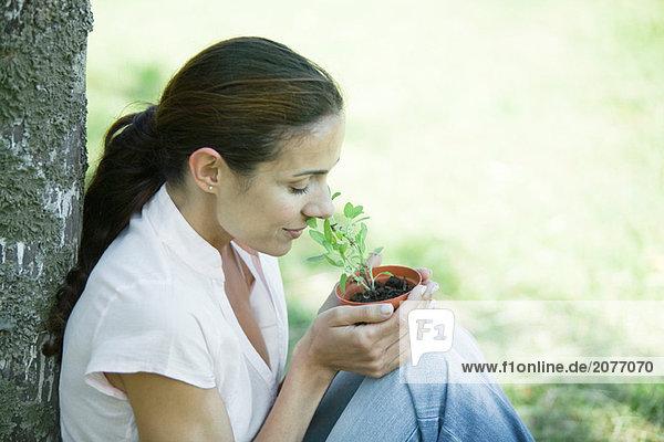 Frau sitzen im Freien  riechen Pot der Kräuter