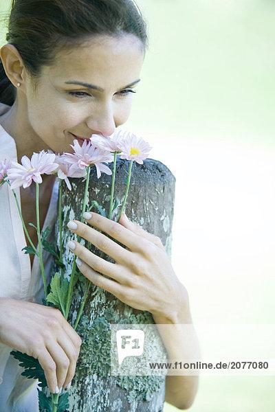 Stützte sich auf Pfosten  Woman smelling flowers