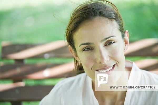 Frau sitzt auf Bank  Lächeln in die Kamera  Portrait
