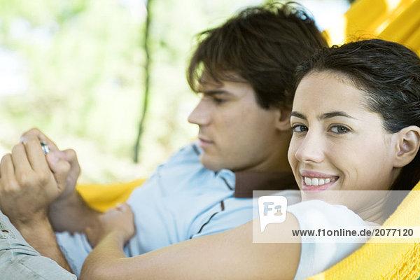 Junges paar liegen in der Hängematte  mit digital-Kamera