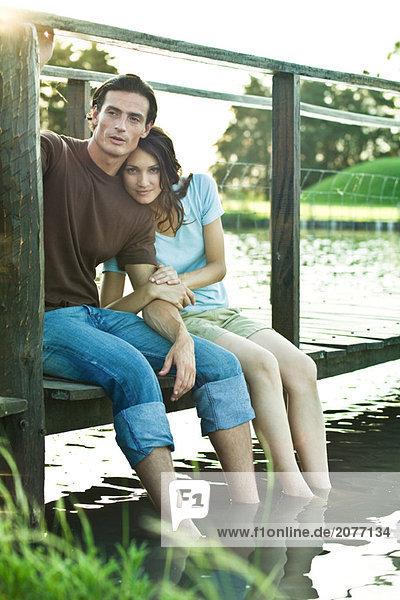 Paar sitzen auf Dock  baumelnd Beine in Wasser  Frau Blick in die Kamera  Ganzkörperansicht