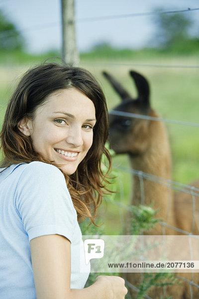 Frau Lächeln in die Kamera  Lama hinter Zaun im Hintergrund