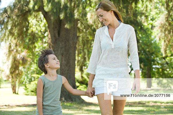 Mutter und Sohn  gehen hand in hand  lächelnd einander